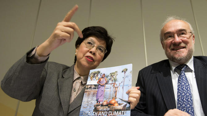 """Director General of the World Health Organization (WHO) Dr. Margaret Chan, left, and Secretary-General of the World Meteorological Organization (WMO) Michel Jarraud pose for the media with the Atlas Of Health And Climate, a manual which provides a practical guide to """"climate-sensitive diseases"""" that decision-makers and leaders can use as a tool for prevention, during a presentation for the media at the International Conference Center in Geneva, Switzerland, Monday, Oct.  29, 2012. (AP Photo/Keystone/Salvatore Di Nolfi)"""