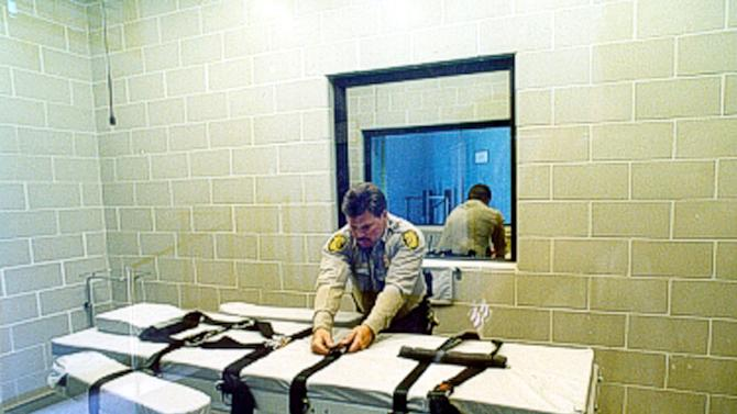 FILE - In this undated file photo provided by the Arizona Department of Corrections, an unidentified Arizona Corrections Officer adjusts the straps on the gurney used for lethal injections at the Arizona State Prison at Florence, Ariz. The prolonged execution this week of an Arizona death row inmate with a new, two-drug combination highlights the patchwork approach states have been forced to take with lethal injection drugs, with the types, combinations and dosages varying widely. (AP Photo/Arizona Department of Corrections)