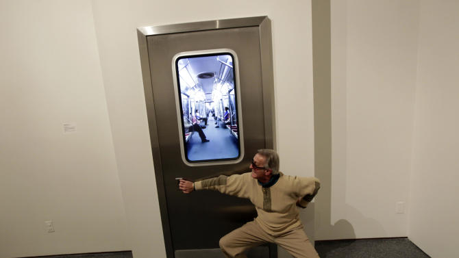 """In this Wednesday, Nov. 14, 2012 photo, museum patron Buz Burzelleri, of New Orleans, clowns for the camera as he pretends to open the door of the installation titled """"Subway,"""" by artist Leadro Erlich, at the New Orleans Museum of Art, in New Orleans. The piece is part of """"Lifelike,"""" a traveling exhibit at the New Orleans Museum of Art through Jan. 27. (AP Photo/Gerald Herbert)"""