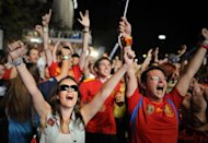 Supporters of the Spanish national football team celebrate after Spain defeated Portugal during the Euro 2012 Championships on a giant screen near the Santiago Bernabeu Stadium in Madrid. Defending champions Spain beat Portugal 4-2 on penalties after their Euro 2012 semi-final finished 0-0 after extra-time