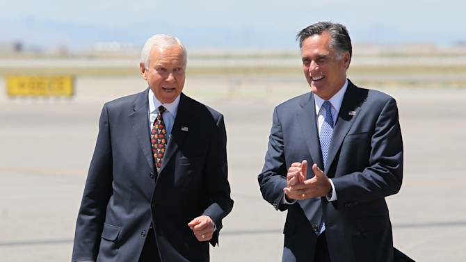 FILE - In this June 8, 2012 file photo, Republican presidential candidate, former Massachusetts Gov. Mitt Romney, right, laughs walking side-by-side with Sen. Orrin Hatch, R-Utah, who met him on the tarmac at Salt Lake International Airport, in Salt Lake City. Local television stations recorded the moment, reminding the state's GOP voters that their favorite politician, Romney, was in Hatch's corner.  (AP Photo/Colin E. Braley, File)