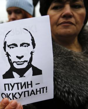 """A woman holds a banner that reads: """"Putin is Occupier"""" during a rally against the breakup of the country in Simferopol, Crimea, Ukraine, Tuesday, March 11, 2014. The Crimean parliament voted Tuesday that the Black Sea peninsula will declare itself an independent state if its residents agree to split off from Ukraine and join Russia in a referendum. Crimea's regional legislature on Tuesday adopted a """"declaration of independence of the Autonomous Republic of Crimea."""" The document specified that Crimea will become an independent state if its residents vote on Sunday in favor of joining Russia in the referendum. (AP Photo/Darko Vojinovic)"""