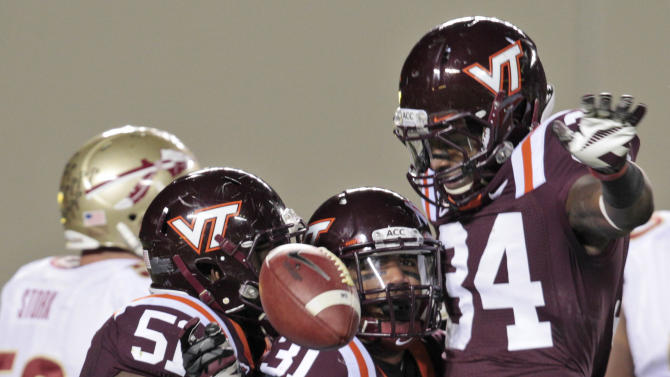 Virginia Tech cornerback Donovan Riley (31) celebrates an interception of a Florida State pass with teammates Bruce Taylor (51) and  Kyshoen Jarrett (34) during the first half of an NCAA college football game in Blacksburg, Va., Thursday, Nov. 8, 2012. (AP Photo/Steve Helber)
