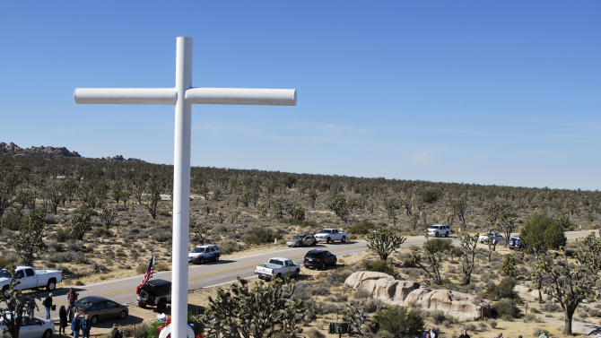 This photo provided by Liberty Institute shows people gathering beneath a 7-foot-tall World War I memorial cross on a rocky hilltop within a national park at its rededication in the Mojave Desert community of Cima, Calif., Sunday, Nov. 11, 2012. An earlier cross had stood on the site since the 1930s, before being deemed unconstitutional and removed because it stood on public land. The site is now in private hands as part of a land swap with the National Park Service that ended the longstanding legal dispute, which had become entangled in the thorny issues of patriotism and religion. (AP Photo/Liberty Institute)