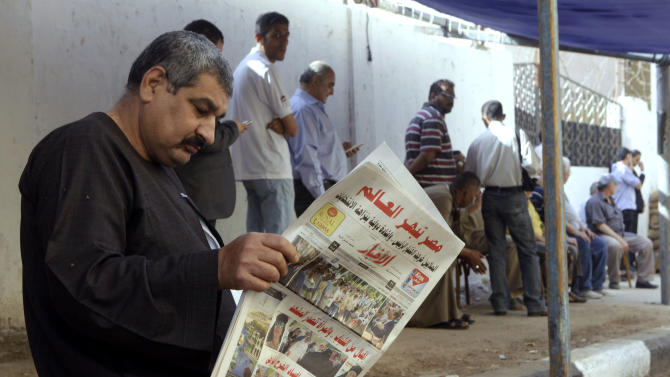 "An Egyptian man reads a local newspaper with the headline in Arabic reading, ""Egypt surprises the world,"" outside a polling station in Cairo, Egypt, Tuesday, May 27, 2014. Egyptians were lining up to vote on Tuesday, the second and final day of the presidential election with the country's former military chief Abdel-Fattah el-Sissi poised for an almost certain victory. (AP Photo/Amr Nabil)"