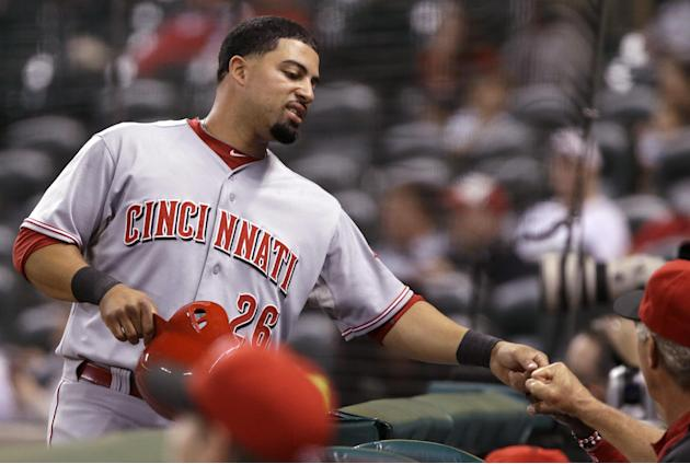 Cincinnati Reds' Xavier Paul (26) is welcomed back to the dugout after scoring on a bases-loaded, two-run single by Zack Cozart in the first inning of an MLB inter-league  baseball game Tuesday, Sept.