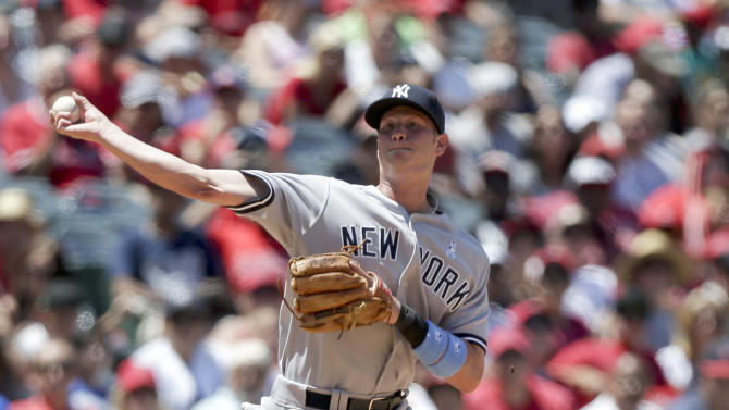 New York Yankees shortstop Reid Brignac throws Los Angeles Angels' Peter Bourjos out at first during the sixth inning of a baseball game in Anaheim, Calif., Sunday, June 16, 2013. (AP Photo/Chris Carlson)