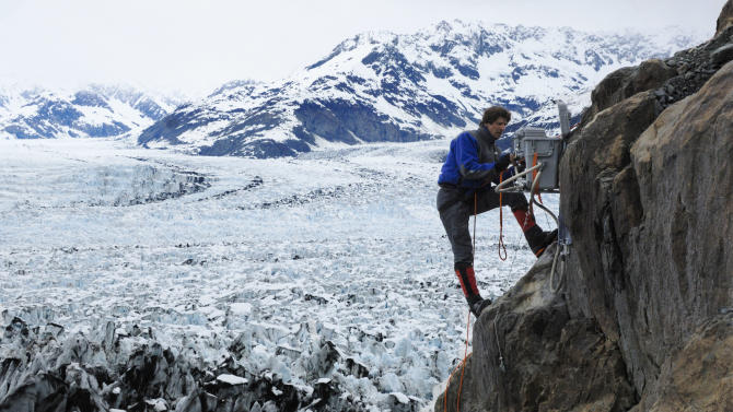 """This 2007 photo released by Extreme Ice Survey shows James Balog installing a """"cliff"""" camera at Columbia Glacier in Alaska for the film, """"Chasing Ice."""" The film, about climate change, follows Balog across the Arctic as he deploys revolutionary time-lapse cameras designed to capture a multi-year record of the world's changing glaciers. (AP Photo/Extreme Ice Survey)"""