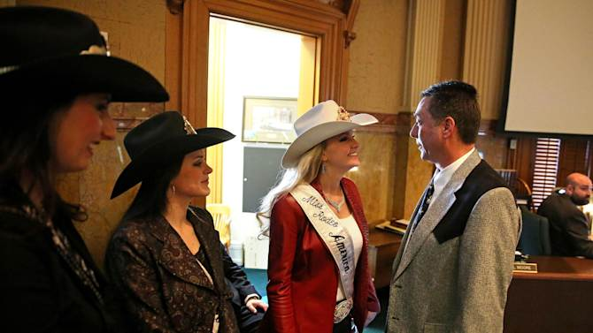 In this Jan. 22, 2014 photo, Colorado state representative Jerry Sonnenberg (R-Sterling) talks with Miss Rodeo America Paige Nicholson, inside the chambers of the Colorado State Legislature, at the Capitol, in Denver. Nicholson and fellow rodeo queens Codi Miller, center, and Ashley Fuchs were in town for the National Western Stock Show. Sonnenberg, a rancher who's the only farmer in the Colorado House, plans to push a radical idea this session: give each of his state's 64 counties one House seat apiece instead of electing representatives from districts with equal populations. ( AP Photo/Brennan Linsley)