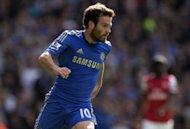 Chelsea's midfielder Juan Mata runs with the ball during their English Premier League football match against Arsenal at The Emirates Stadium in north London, England. Chelsea remained on top of the Premier League as Mata inspired them to a 2-1 win over London rivals Arsenal