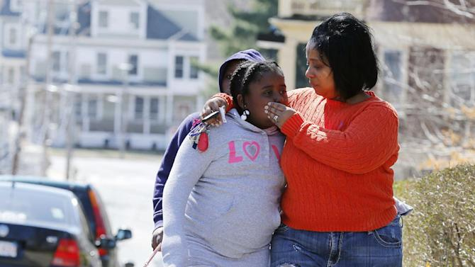FILE - Tammy Lynch, right, comforts her daughter Kaytlyn, 8, after leaving flowers and some balloons at the Richard house in the Dorchester neighborhood of  Boston, Tuesday, April 16, 2013. Kaytlyn was paying her respects to her friend, 8-year old Martin Richard who was killed in Monday's bombings at the finish line of the Boston Marathon. (AP Photo/Michael Dwyer)
