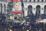 Anti-government protesters stand front of a poster showing jailed Ukrainian opposition leader Yulia Tymoshenko in the Independence Square in Kiev February 22, 2014. REUTERS/Vasily Fedosenko