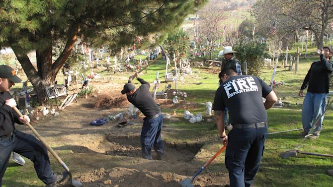 """Members of the Tule River Indian Reservation Fire Department help to dig the grave Monday Dec. 10, 2012 of a tribal member who died recently of natural causes. Afterward, they said they would move to the other side of the colorfully decorated cemetery for the somber task of digging a grave for 8-year-old Alyssa Celaya, who was murdered along with her grandmother and two other relatives on Sunday. Her father, 31-year-old Hector Celaya, is suspected in the killings and died in a shootout with Tulare County sheriff's deputies. The men said that they dig graves by hand instead of using backhoes or other machinery """"out of respect."""" But never have they had to dig so many at once. All told, 5 residents of the reservation are dead. (AP Photo/Tracie Cone)"""