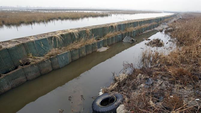 In this Dec. 8, 2012 photo, the Richard P. Kane Wetland Mitigation Bank, a long barrier wall made of large baskets filled with sand and dirt, runs through the Meadowlands in Moonachie, N.J. The barrier was built primarily to control the movement of tidewaters in and out of the wetlands area and not for flood protection. But since the tidal surge from Superstorm Sandy washed over it and damaged more than 2,000 homes and other buildings, attention has turned to what can be done to prevent similar river flooding in future storms. Unfortunately, however, no one seems to own the problem. (AP Photo/Mel Evans)