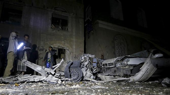 Police officers inspect the site of a car bomb attack in Yemen's capital Sanaa