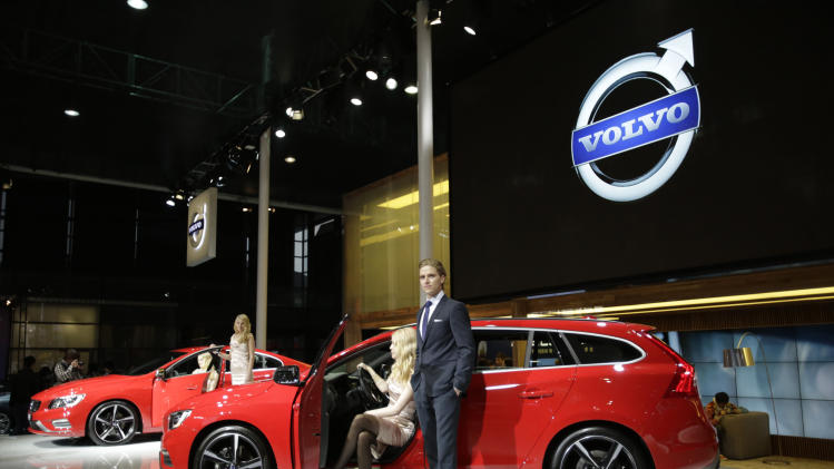 Models pose next to a Volvo S60 R-Design, back, and a V60 R-Design, forward, at the Shanghai International Automobile Industry Exhibition (AUTO Shanghai) media day in Shanghai, China Saturday, April 20, 2013. (AP Photo/Eugene Hoshiko)