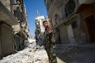 A Syrian rebel stands in a heavily damaged street in the Salaheddin district of the northern city of Aleppo. Grisly footage has emerged appearing to show rebels in the Aleppo area callously throwing bodies off a post office building, while another video showed a man, blindfolded and bound, as his throat was savagely cut