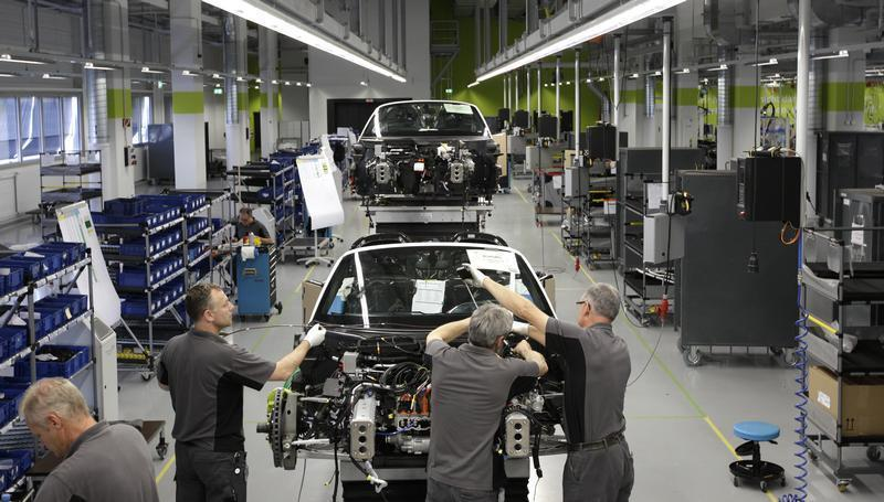 Electricians assemble new Porsche 918-Spyder sports car at production line of German car manufacturer's plant in Stuttgart