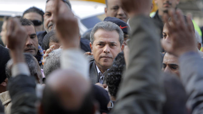 Tawfiq Okasha, center, a popular Egyptian TV presenter, is greeted by his supporters as he arrives at the Cairo South court in Cairo Egypt, Tuesday, Jan. 8, 2013. An Egyptian court acquitted Okasha on charges of inciting the killing of the country's new president Mohammed Morsi. (AP Photo/Amr Nabil)