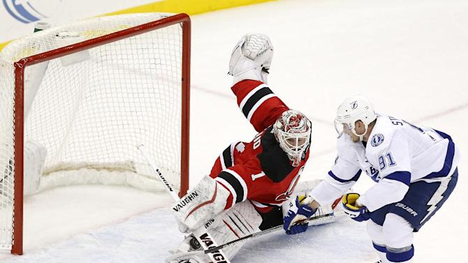 New Jersey Devils goalkeeper Keith Kinkaid (1) makes a save on a shot by Tampa Bay Lightning center Steven Stamkos (91) during a shootout in an NHL hockey game, Friday, Dec. 19, 2014, in Newark, N.J. Kinkaid recorded his first career victory with the Devils' 3-2 win. (AP Photo/Julio Cortez)