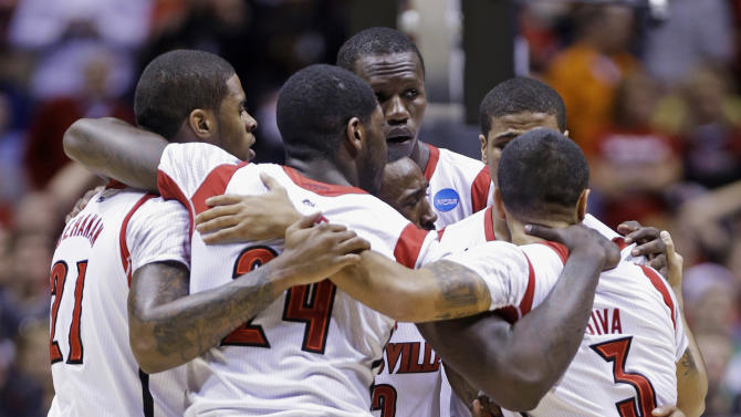 Louisville players huddle as guard Kevin Ware is treated for an injury during the first half of the Midwest Regional final against Duke in the NCAA college basketball tournament, Sunday, March 31, 2013, in Indianapolis. (AP Photo/Michael Conroy)