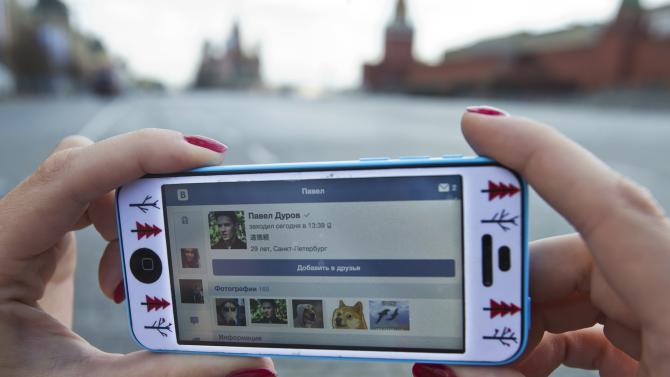 A user of Russia's leading social network internet site VKontakte, poses holding an iPhone showing the account page of Pavel Durov, the former CEO and founder of VKontakte, in Red Square in Moscow, Russia, Wednesday, April 23, 2014. The network's founder, Pavel Durov, described as Russia's Mark Zuckerberg (founder of Facebook), left his post as CEO on Tuesday April 22, 2014, and is reported to have left Russia, one week after he posted online what he said were documents from the security services demanding personal details from 39 Ukraine-linked groups on VKontakte.(AP Photo/Pavel Golovkin)