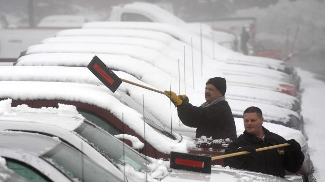 Sales consultants Jerry Baier, left, 44, of Romeo, and Earl Culver, 46, of Macomb Twp., clean snow off Chevy Silverados at Heidebreicht Chevrolet  in Washington Twnshp. Wednesday, Feb. 27, 2013, as fog also envelopes Northern Macomb County. (AP Photo/The Detroit News, Todd McInturf)