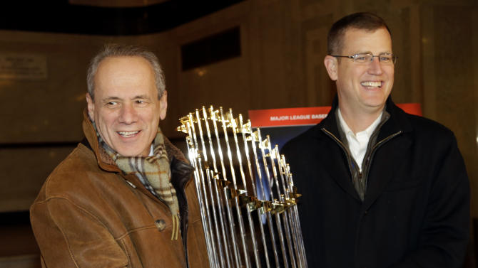 """FILE - In this Nov. 23, 2013 file photo, Boston Red Sox CEO Larry Lucchino, left, and Chief Operating Officer Sam Kennedy hold the 2013 World Series baseball trophy on the red carpet at the Wang Theatre before a screening of a DVD about the series in Boston. Lucchino said Friday, Feb. 21, 2014, that he views the big-spending New York Yankees and his more frugal team as """"very different animals."""" (AP Photo/Steven Senne, File)"""