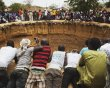 People watch a traditional ceremony taking place in a large former well in the village of Ndande