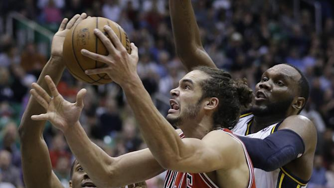 Chicago Bulls' Joakim Noah (13) drives to the basket as Utah Jazz's Derrick Favors, left, and teammate Al Jefferson, right, defend in the fourth quarter during an NBA basketball game Friday, Feb. 8, 2013, in Salt Lake City. The Bulls defeated the Jazz 93-89. (AP Photo/Rick Bowmer)