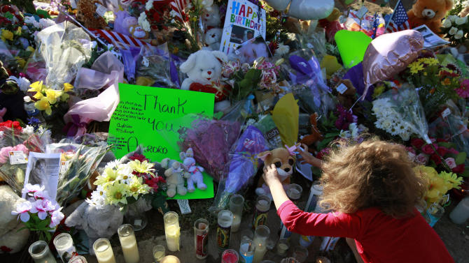 """Serenity Brydon, 7, places a rosary around a bear at a memorial near the the Century 16 movie theater Sunday, July 22, 2012, in Aurora, Colo. Twelve people were killed and dozens were injured in a shooting attack early Friday at the packed theater during a showing of the Batman movie, """"The Dark Knight Rises."""" Police have identified the suspected shooter as James Holmes, 24. (AP Photo/Alex Brandon)"""
