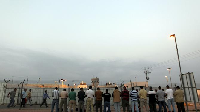 File photo shows Palestinian labourers praying after crossing through checkpoint near Qalqilya