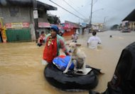 <p>A resident pushes an improvised inflatable boat loaded with his dog through flood waters as they head for a safer area in the village of Tumana, Marikina town, in suburban Manila on August 7, 2012, after torrential rains inundated most of the capital.</p>