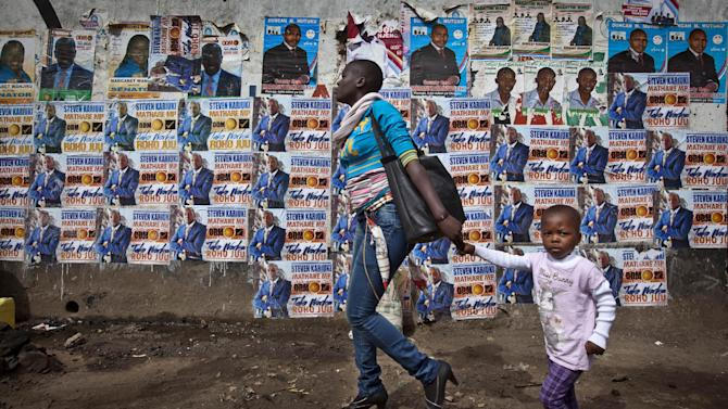 In this photo taken Tuesday, Feb. 26, 2013, a mother and her child walk past a wall plastered with election campaigning posters in the Mathare slum of Nairobi, Kenya. Kenya on Monday holds its first presidential election since its 2007 vote devolved into months of tribal violence, and in recent weeks in Nairobi's most dangerous slum Mathare dozens of tin shack homes have been burned to the ground and some families are moving into zones controlled by their own clans. (AP Photo/Ben Curtis)