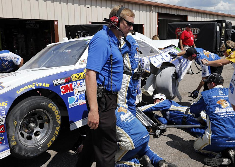 Crew members look at Mark Martin's car in the garage area during the NASCAR Sprint Cup Pure Michigan 400 auto race at Michigan International Speedway, Sunday, Aug. 19, 2012, in Brooklyn, Mich. (AP Photo/Bob Brodbeck)