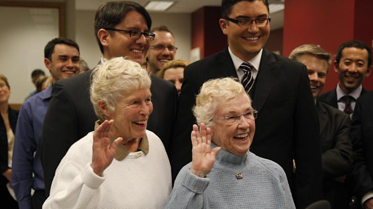 Jane Abbott Lighty, left, and her partner Pete-e Petersen raise their right hands as they take an oath while receiving the first marriage license for a same-sex couple in King County, Thursday, Dec. 6, 2012, in Seattle. Behind Lighty and Petersen are Brendon K. Taga, left, and Jesse Page. King County Executive Dow Constantine began issuing the licenses immediately upon certification of the November election that passed Referendum 74. (AP Photo/Elaine Thompson)