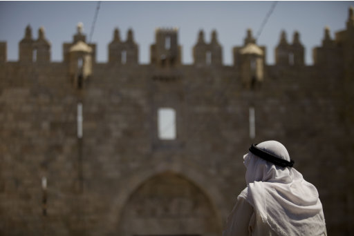 A Palestinian man stands outside the Damascus Gate of Jerusalem's Old City, on the last Friday of the Muslim holy month of Ramadan, Friday, Aug. 26, 2011. Muslims around the world are observing the holy fasting month of Ramadan where they refrain from eating, drinking, smoking from dawn to dusk. (AP Photos/Dan Balilty)