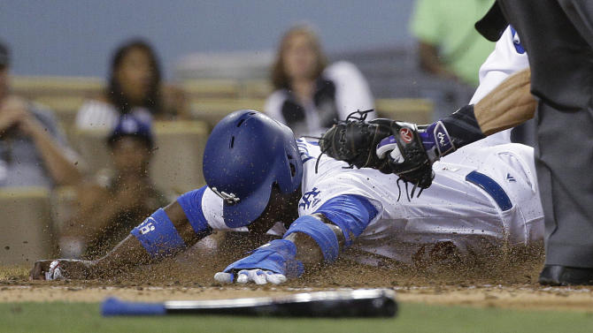 Los Angeles Dodgers' Yasiel Puig is tagged out by Colorado Rockies catcher Nick Hundley as he tried to score on a fly ball hit by Trayce Thompson during the seventh inning of a baseball game Friday, July 1, 2016, in Los Angeles. (AP Photo/Jae C. Hong)