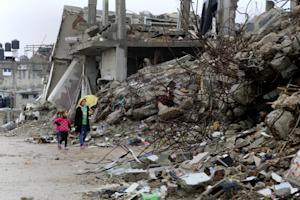Palestinian girls walk past destroyed homes from recent …