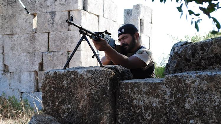 "This citizen journalism image provided by Shaam News Network SNN, taken on Monday, July 4, 2012, purports to show a Free Syrian Army soldier aiming his weapon in the northern town of Sarmada, in Idlib province, Syria. Syria's military began large-scale exercises simulating defense against outside ""aggression,"" the state-run news agency said Sunday an apparent warning to other countries not to intervene in the country's crisis. (AP Photo/Shaam News Network, SNN)THE ASSOCIATED PRESS IS UNABLE TO INDEPENDENTLY VERIFY THE AUTHENTICITY, CONTENT, LOCATION OR DATE OF THIS HANDOUT PHOTO"