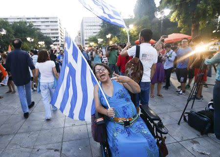 A woman in a wheelchair celebrate the results of the first exit polls in Syntagma Square in Athens