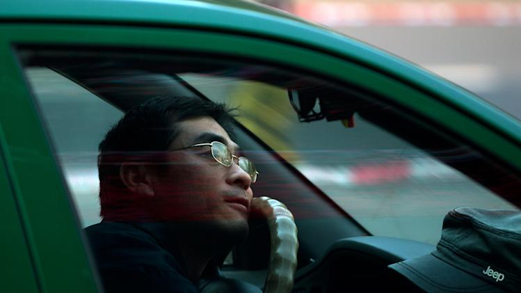 A taxi driver sits inside his car watching a TV screen showing a live broadcast of China's new Communist Party General Secretary Xi Jinping speaking during a press event to introduce the newly-elected members of the Politburo Standing Committee, at a shopping mall in Beijing Thursday, Nov. 15, 2012. The seven-member Standing Committee, the inner circle of Chinese political power, was paraded in front of assembled media on the first day following the end of the 18th Communist Party Congress. (AP Photo/Andy Wong)
