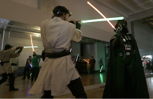 Golden Gate Knights instructor Alain Block, left, and Gary Ripper, dressed as Darth Vader, demonstrate light saber moves during class in San Francisco, Sunday, Feb. 10, 2013. A group of San Francisco