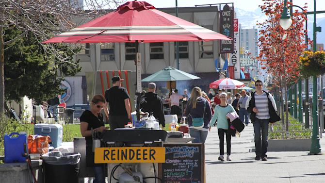 This photo taken June 7, 2013, shows hot dog vendors, or in this case reindeer dog vendors, set up in downtown, Anchorage, Alaska. There's plenty of cultural, historical and fun activities to do in Anchorage for cruise ship passengers who don't want to pay for expensive excursions. (Photo/Mark Thiessen)