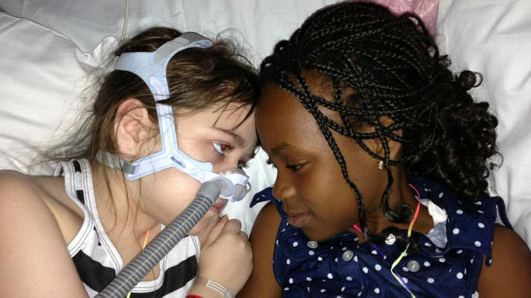 FILE - In this May 30, 2013 file photo provided by the Murnaghan family, Sarah Murnaghan, left, lies in her hospital bed next to adopted sister Ella on the 100th day of her stay in Children's Hospital of Philadelphia. A federal judge in Philadelphia has made the dying 10-year-old eligible to seek donor lungs from an adult transplant list. (AP Photo/Murnaghan Family, File)