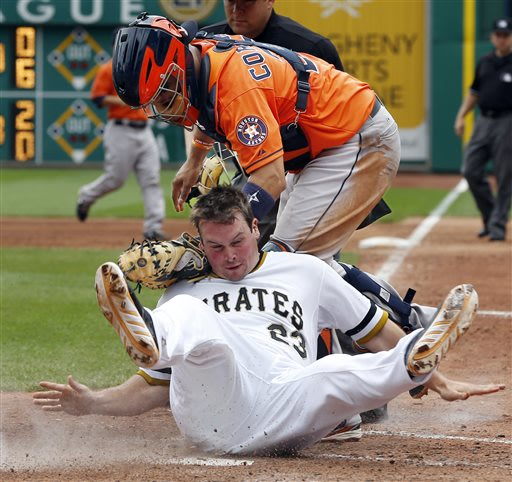 Pittsburgh Pirates' Travis Snider, bottom, rolls into Houston Astros catcher Carlos Corporan after being tagged out trying to score from second on a single by Gaby Sanchez in the sixth inning of a bas