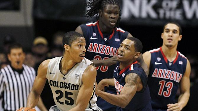 Colorado guard Spencer Dinwiddie (25) looks to pass the ball under pressure from Arizona guard Mark Lyons, front right, as forward Angelo Chol, rear left, and guard Nick Johnson cover in the second half of their NCAA college basketball game in Boulder, Colo., Thursday, Feb. 14, 2013. (AP Photo/David Zalubowski)