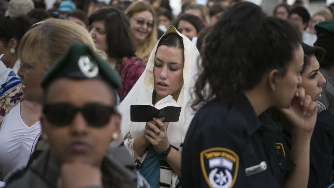 """An Israeli Jewish women of the Woman of the Wall organization prays while wearing a prayer shawl at the Western Wall, the holiest site where Jews can pray in Jerusalem's old city, Sunday, June 9, 2013. The group, known as """"Women of the Wall,"""" convenes monthly prayer services at the Western Wall, wearing prayer shawls and performing rituals that ultra-Orthodox Jews believe only men are allowed to do. (AP Photo/Michal Fattal) ISRAEL OUT"""