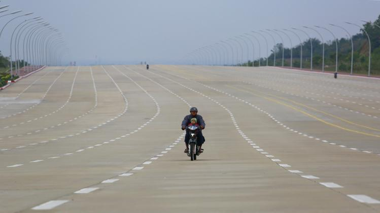A man rides his motorcycle with a child on an empty 20-lane road in Naypyitaw