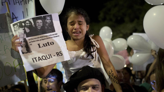 A girl cries during a march in a plaza near the Kiss nightclub honoring the victims of early Sunday's fatal fire inside the club in Santa Maria, Brazil, Monday, Jan. 28, 2013. All the elements were in place for the tragedy at the Kiss nightclub early Sunday. The result was the world's worst fire of its kind in more than a decade, with 231 people dead and this southern Brazilian college town in shock and mourning.(AP Photo/Felipe Dana)